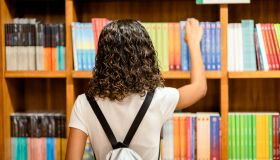 Young girl looking at books on shelves in a bookstore