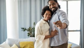 Portrait of couple holding keys of their new home