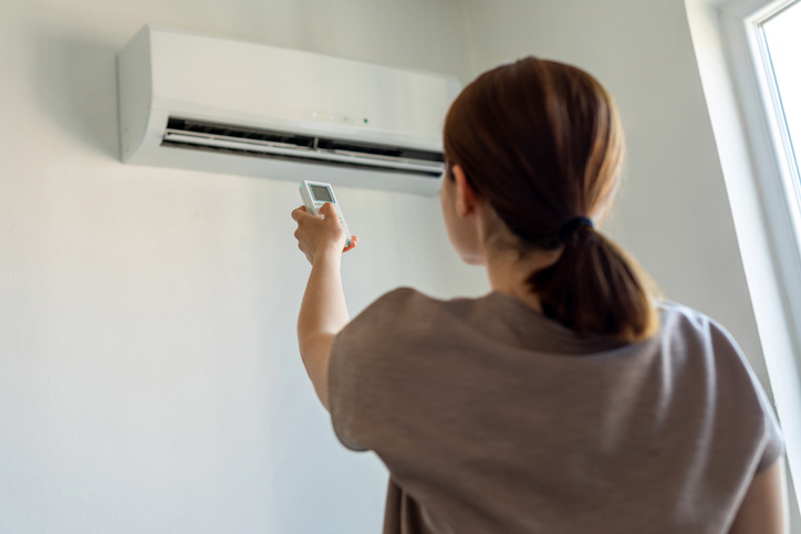 Woman turning on air conditioner with remote