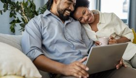 Lovely couple relaxing at home and using laptop