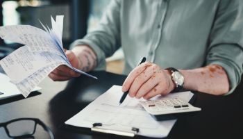 Shot of an unrecognizazble businessman doing paperwork in an office at work
