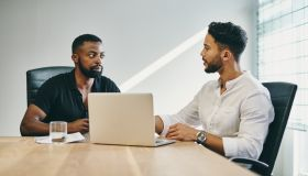 Shot of a young businessmen using a laptop during a meeting in a modern office