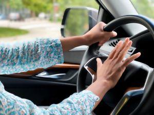 black woman beeps her car horn in traffic