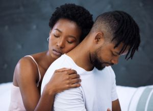 Shot of a young woman hugging her husband in bed at home