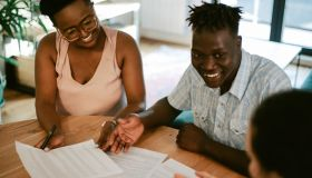 Young couple signing property papers with the real estate agent