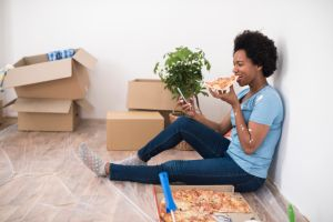African American woman taking pizza break while renovating her apartment