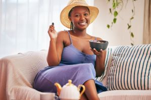Portrait of a young beautiful woman wearing a sunhat and having breakfast on the sofa at home