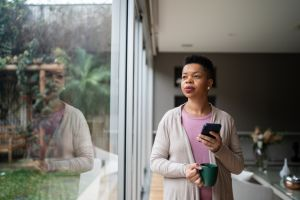 Woman contemplating holding a mug and a smartphone at home