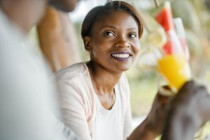 Happy black couple enjoying in summer drink at a cafe.