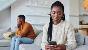 Shot of a young woman ignoring her partner while using a cellphone at home